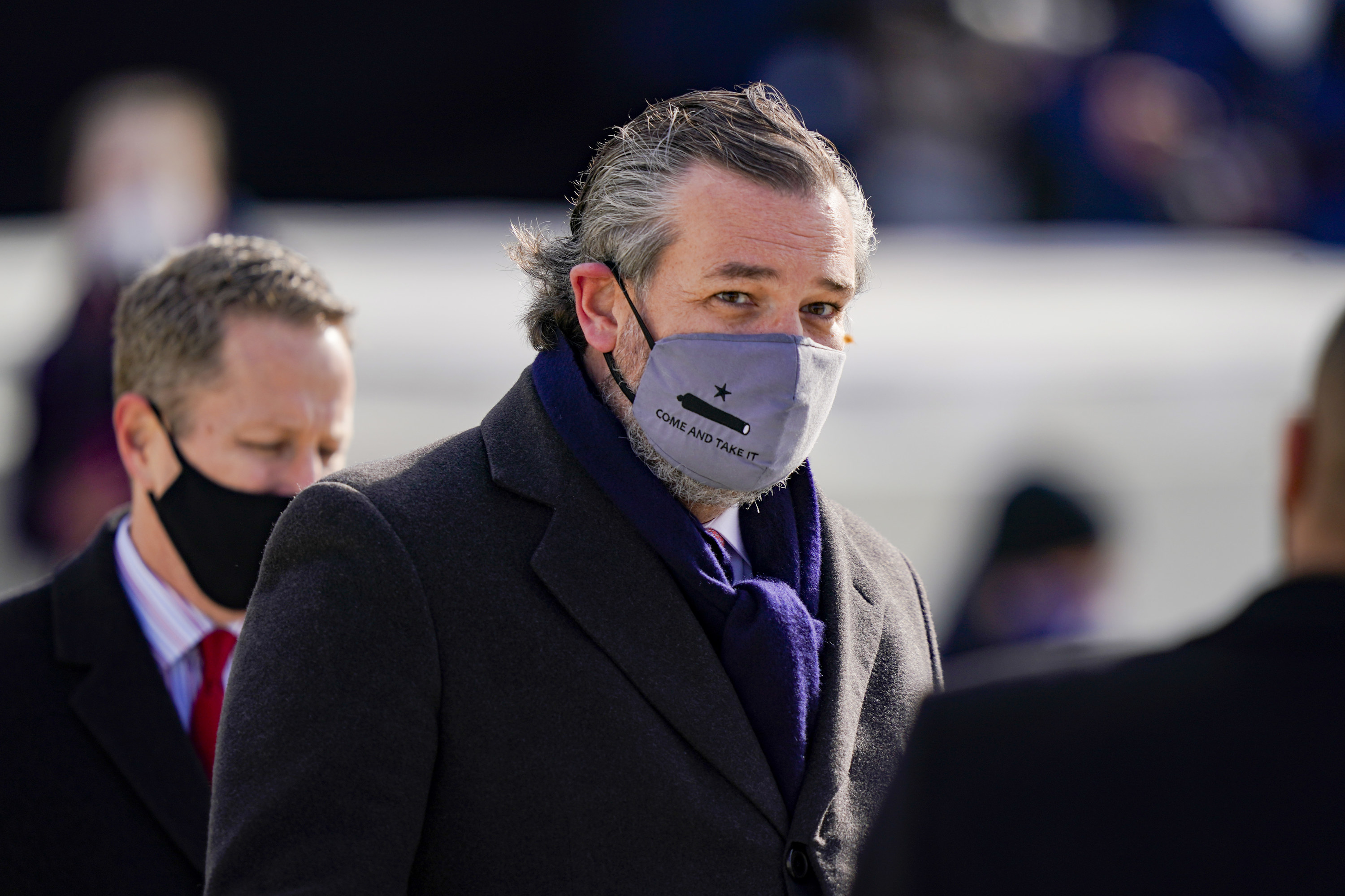"""Ted Cruz wearing a grey face mask that reads """"Come and Take It"""" at the inauguration."""