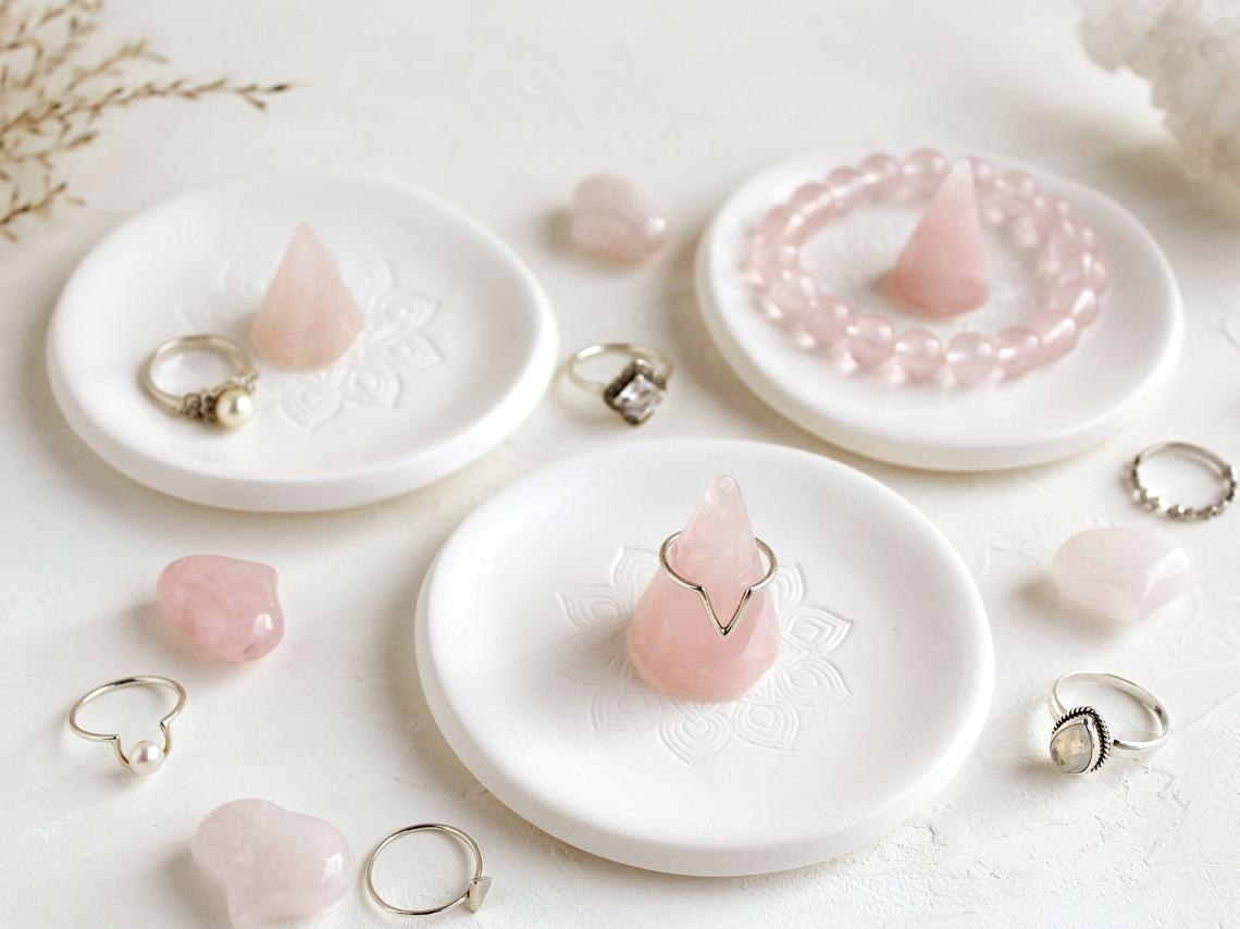 Three rose quartz crystal ring dishes with rings, gemstones, and a bracelet