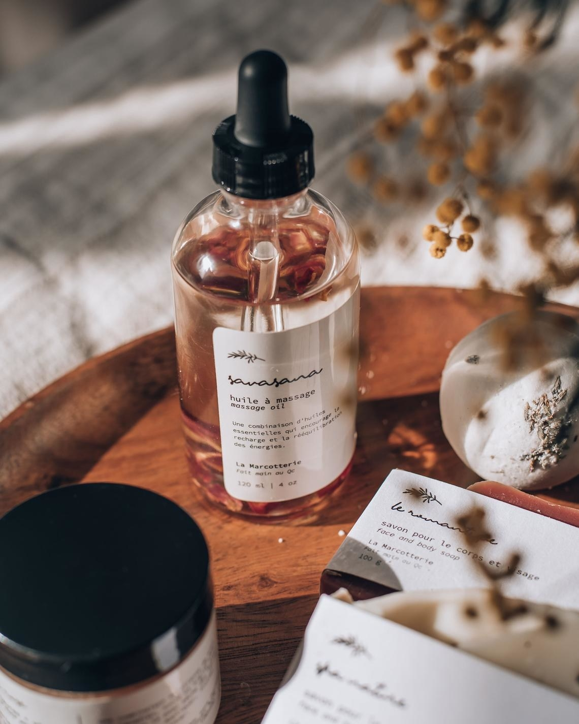 The massage oil on a wooden tray next to other miscellaneous toiletries