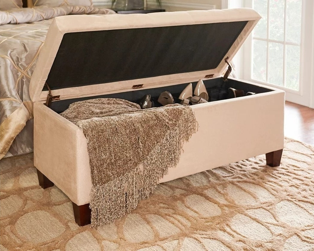 the beige ottoman with a blanket and shoes stored inside