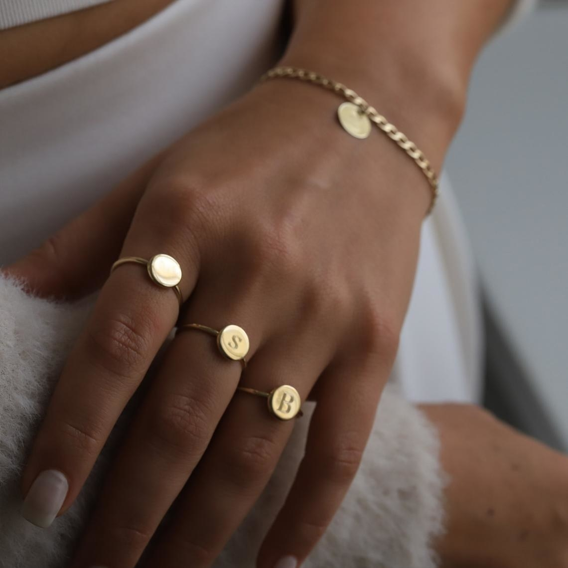 A person wearing three rings, two of which have letters on them