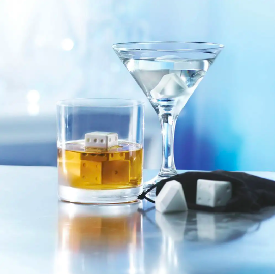A cocktail and martini glass filled with the dice and diamond shaped chilling stones