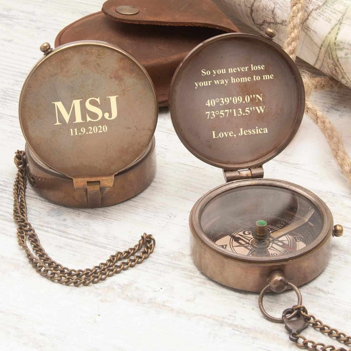 The front and inside of the compass with its leather case in the back ground