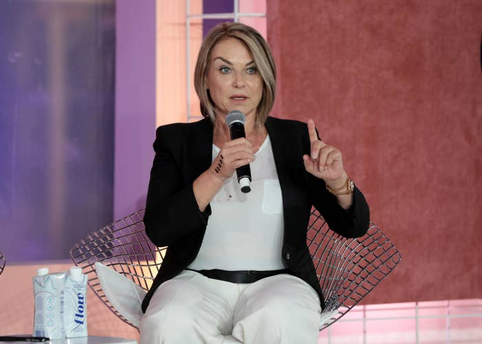 Esther Perel sitting as she holds up one finger at a live event