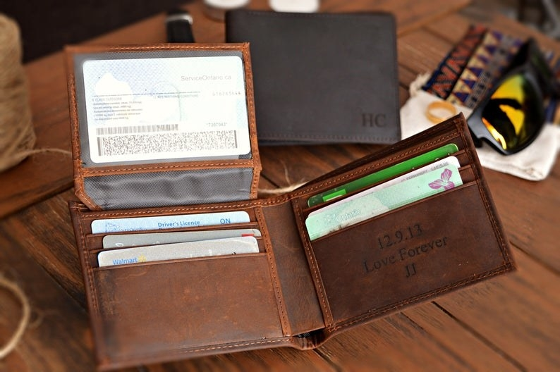 Two leather wallets, one with initials engraved on the front, the other with a message engraved on the inside