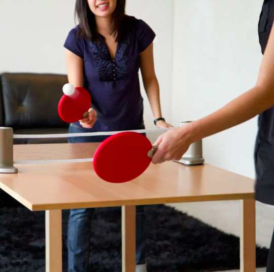 Two people playing ping pong on a dining table