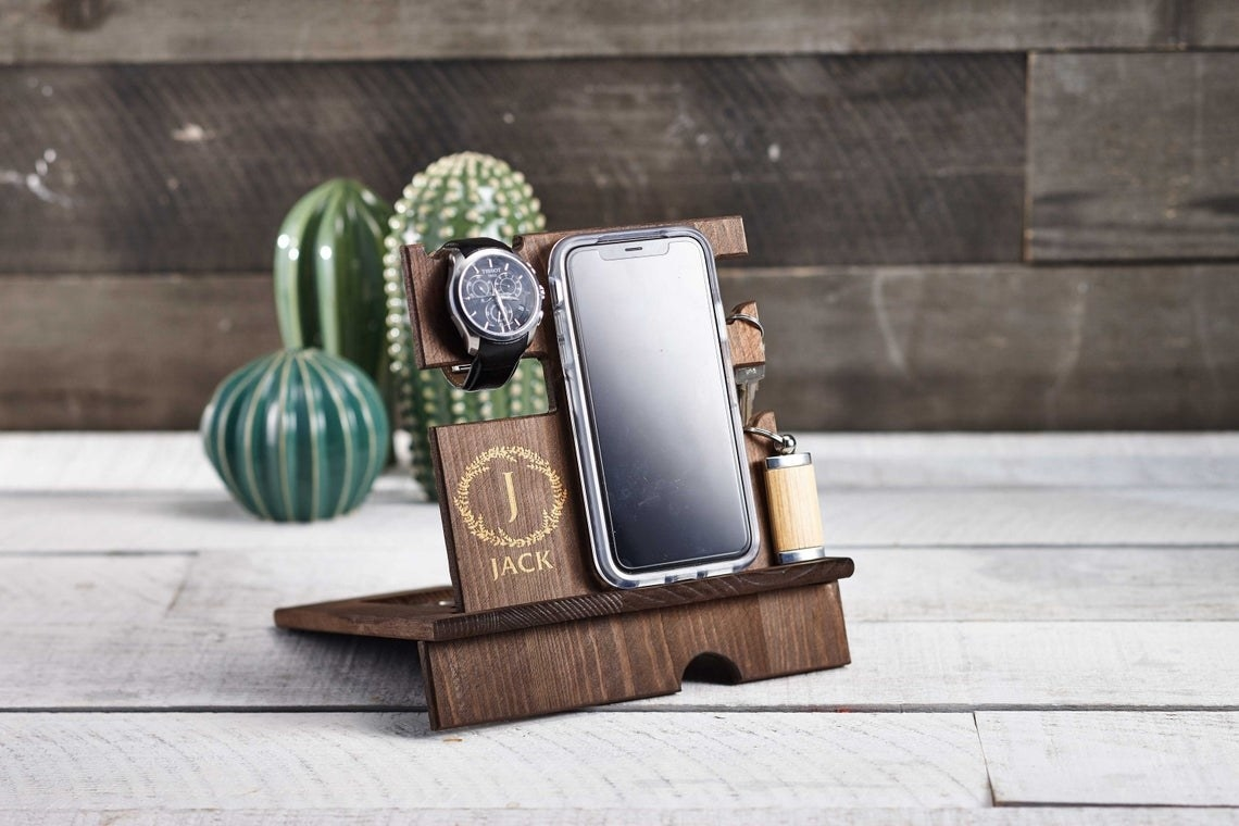 A wooden desk caddy with a phone, watch and keys on it