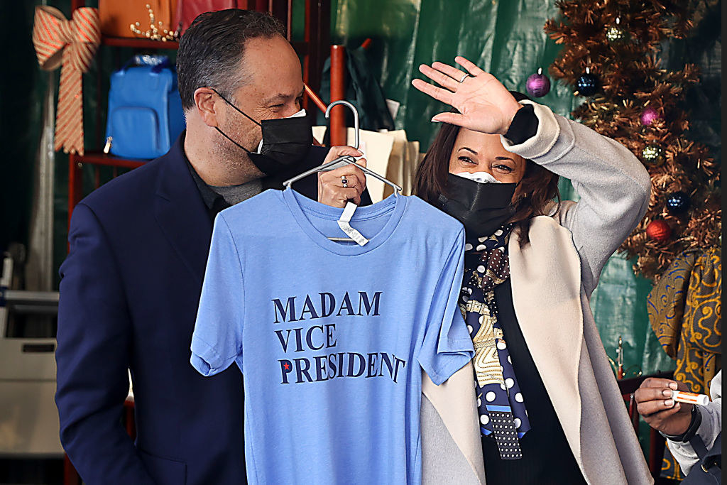 Kamala Harris holding up a shirt that says Madam Vice President