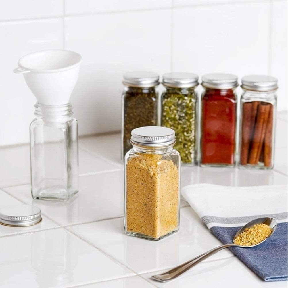 glass bottles filled with spices with one that has a funnel in it