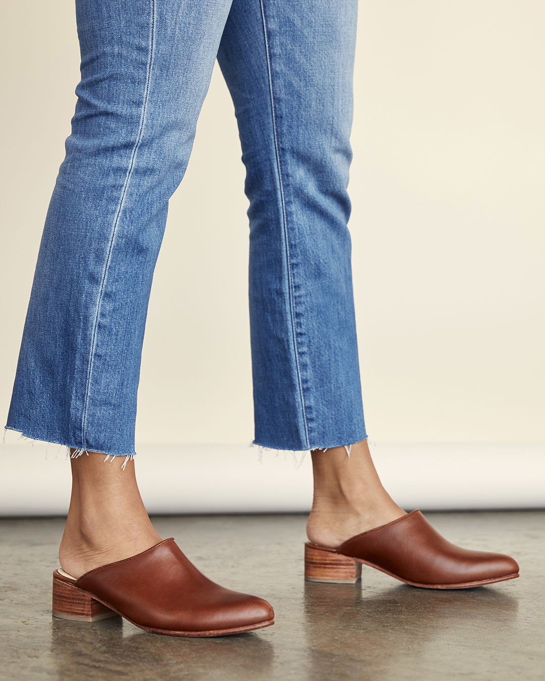 Model wears brown closed-toe mules with straight-leg blue jeans