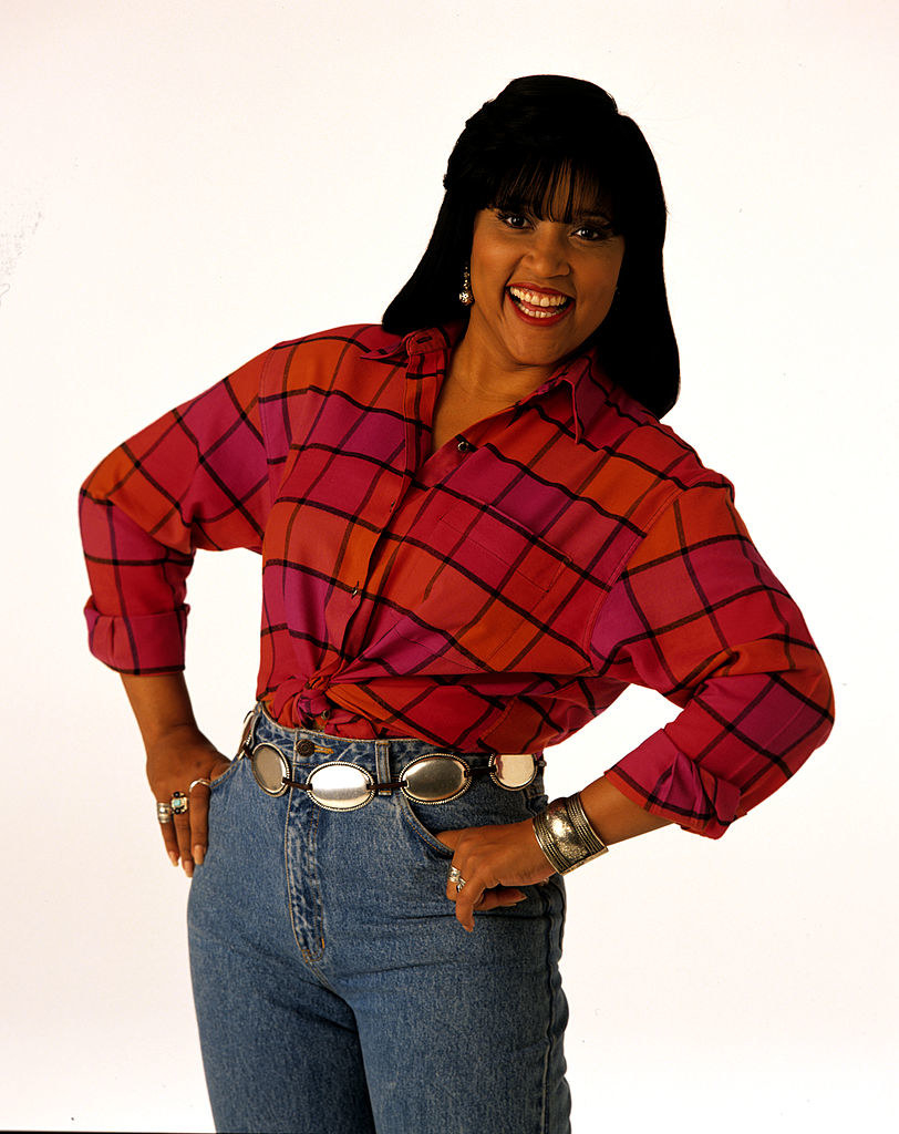 Jackée Harry is posing in a patterned shirt and jeans with her hands in her pocket and her body slightly tilted