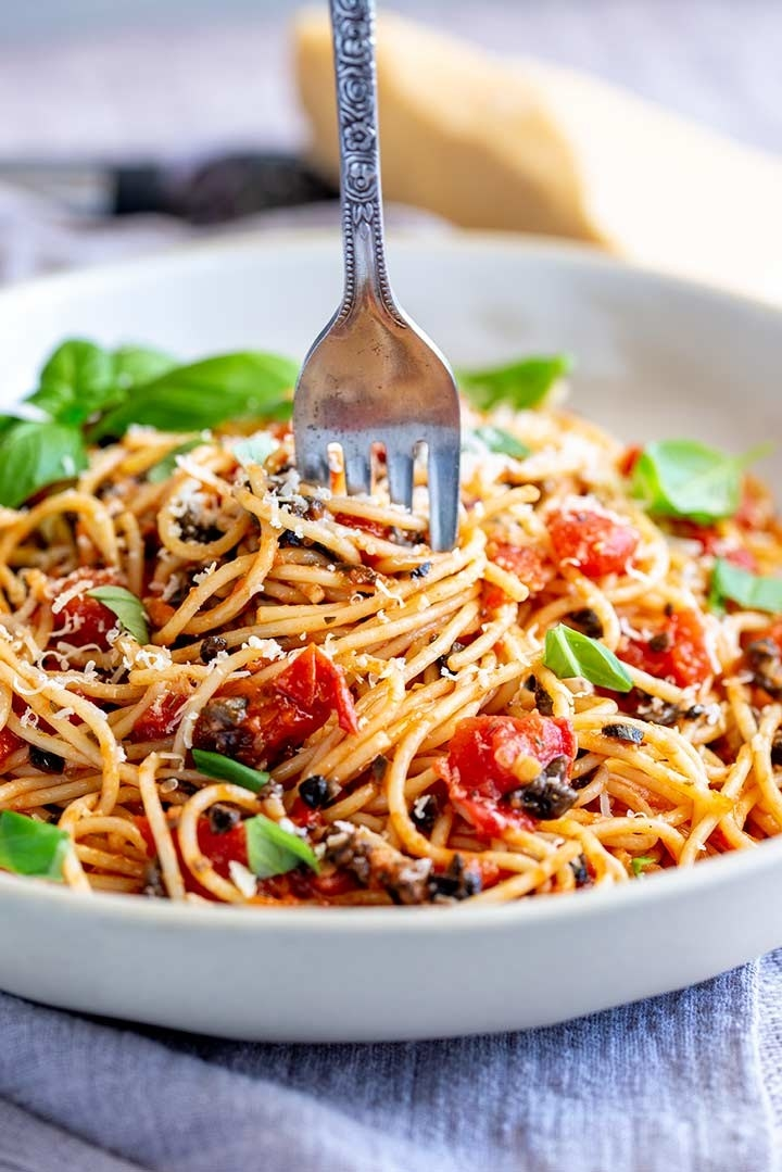 A bowl of spaghetti puttanesca with tomatoes, capers, and olives.