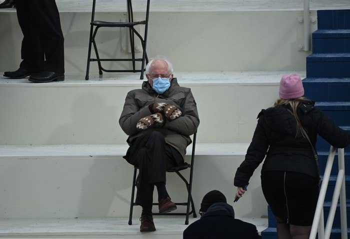Bernie Sanders sitting on a folding chair wearing a coat, wool mittens, and a mask with his arms crossed