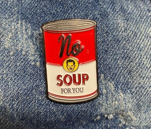 """An enamel pin shaped like a soup can that says """"No soup for you"""" with a small illustration of a mustached face in the center"""