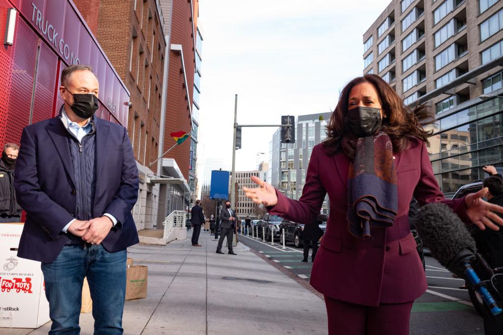 Doug Emhoff standing to the side as Kamala Harris speaks to the press