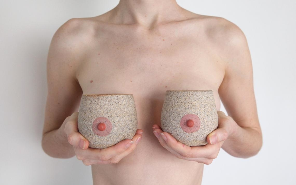 Shirtless person holding boob-shaped mugs in front of chest