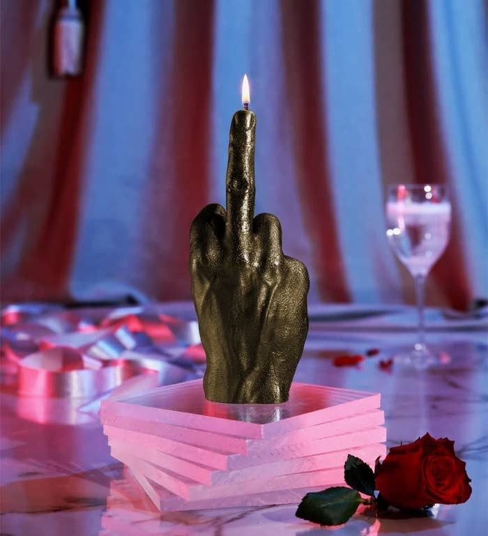 Hand shaped candle with flame starting at upturned middle finger