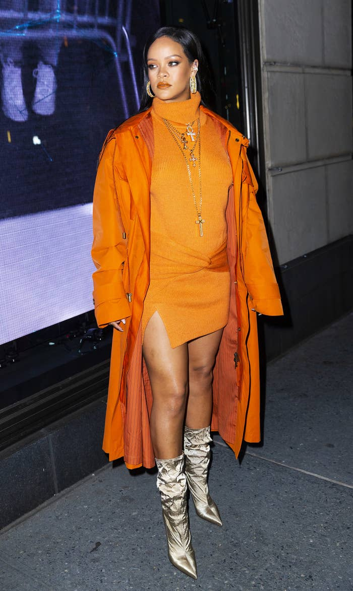 Rihanna arrives wearing a knit turtleneck dress and matching long coat and boots at Bergdorf Goodman to introduce her Fenty Collection