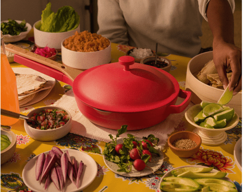 Closeup of the pot and lid in red with the spatula attached to the handle and the lid on top surrounded by food