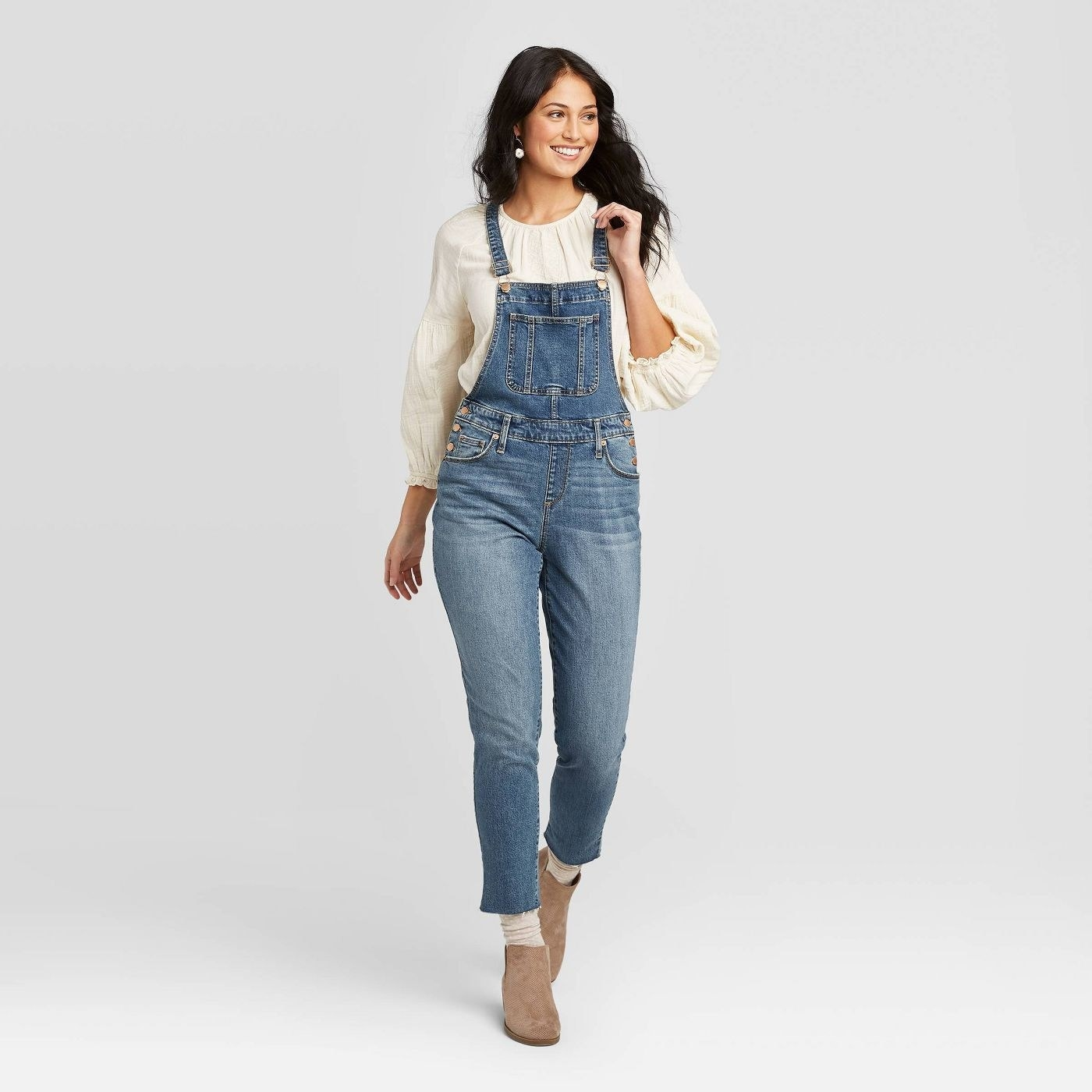 a model in a white blouse and denim overalls