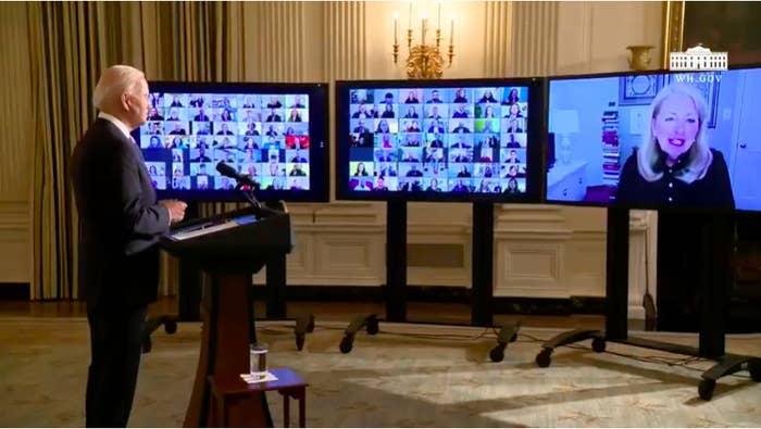 Three screens show dozens of faces watching Biden