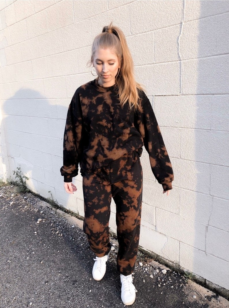 Model wears black and brown tie-dye sweatshirt and sweatpants set with white sneakers
