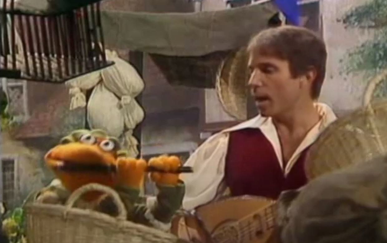 Scooter plays a lute as Paul Simon sings