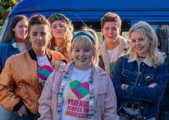 The cast of Derry Girls smile at the camera