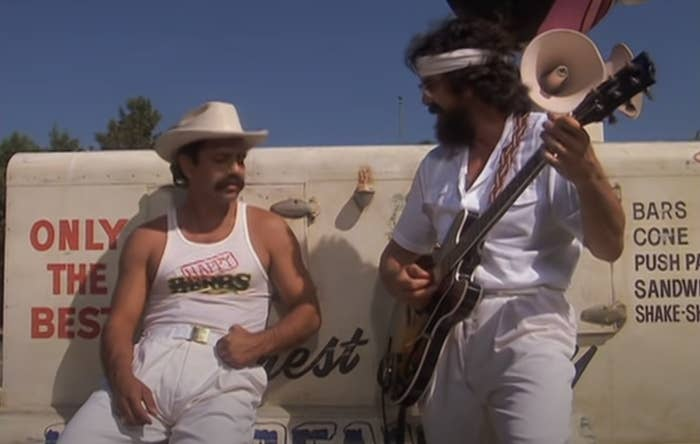 Cheech leans against a truck while Chong plays guitar