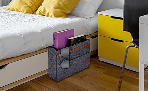 A grey bedside caddy next to a bed