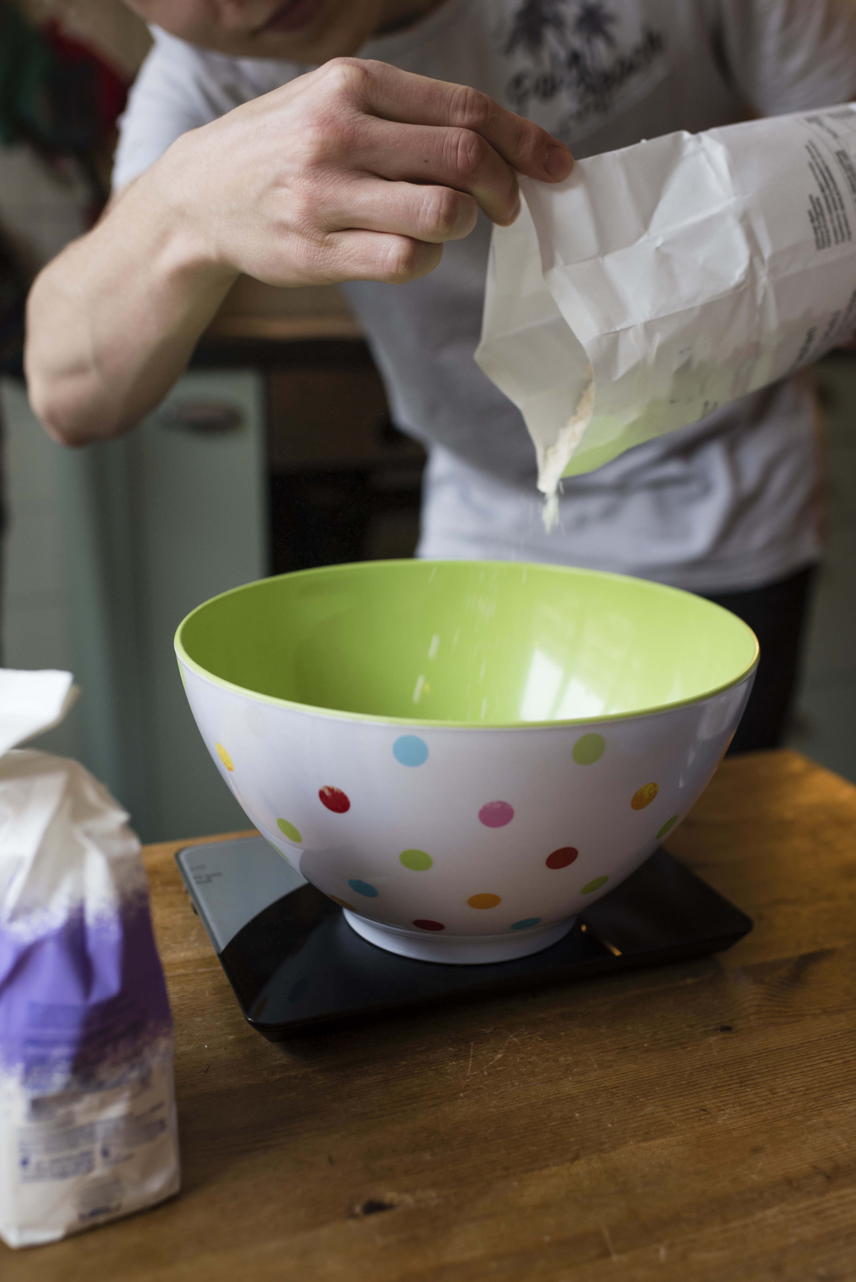 Weighing flour and adding it from a paper bag to a bowl to prepare the cookie dough.