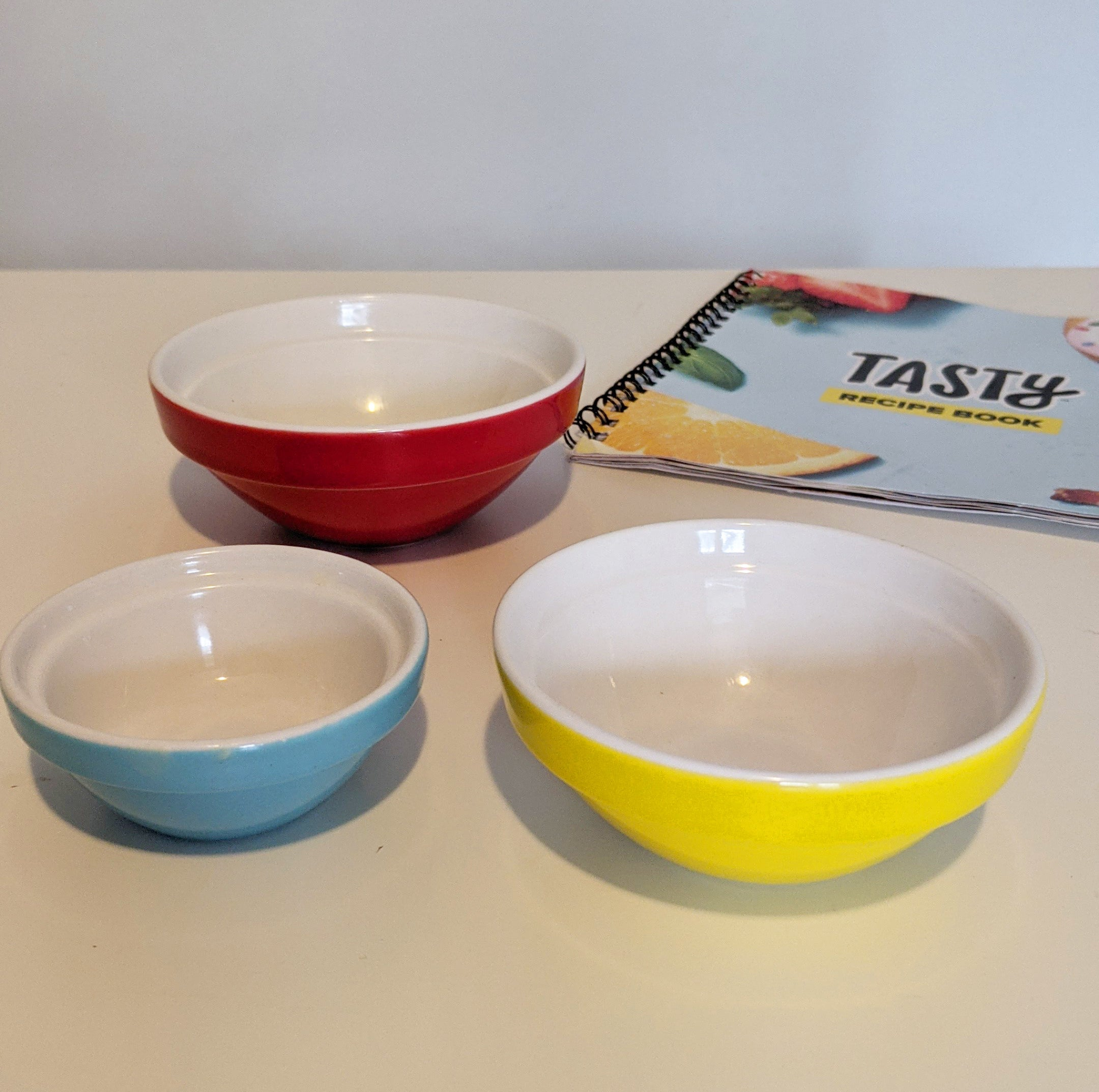 Three pinch bowls of different sizes on a table with a recipe book