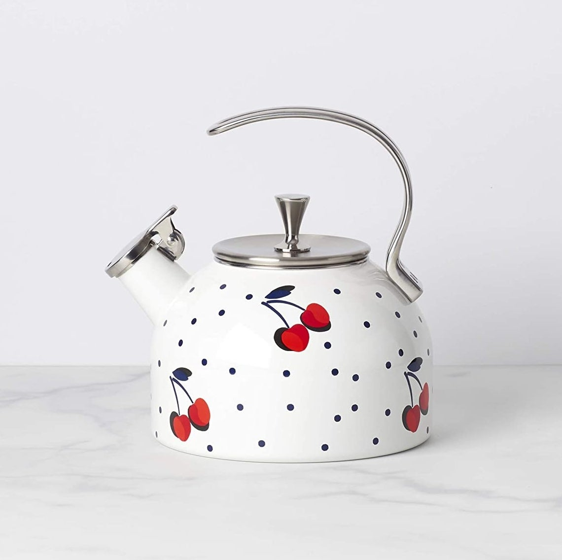 The polka-dotted white kettle which has a cherry pattern