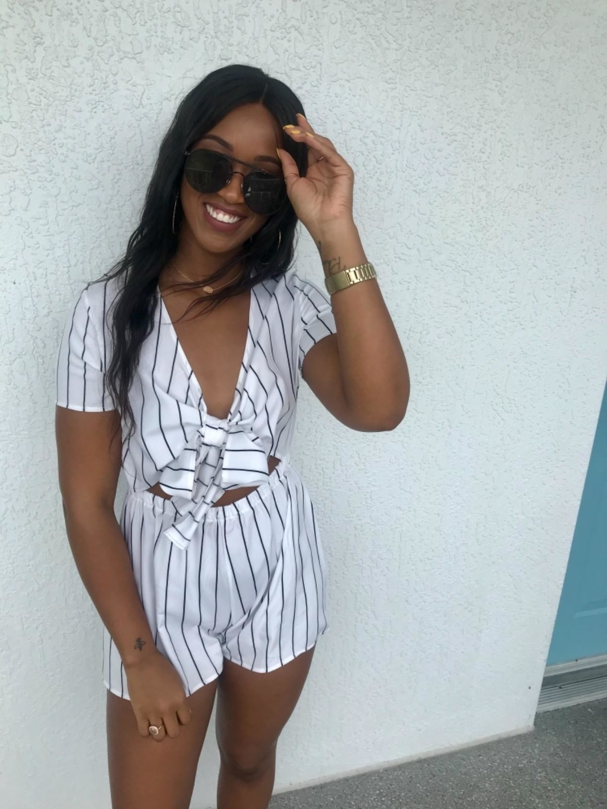 Reviewer wears tie-front short-sleeve black and white romper with shades