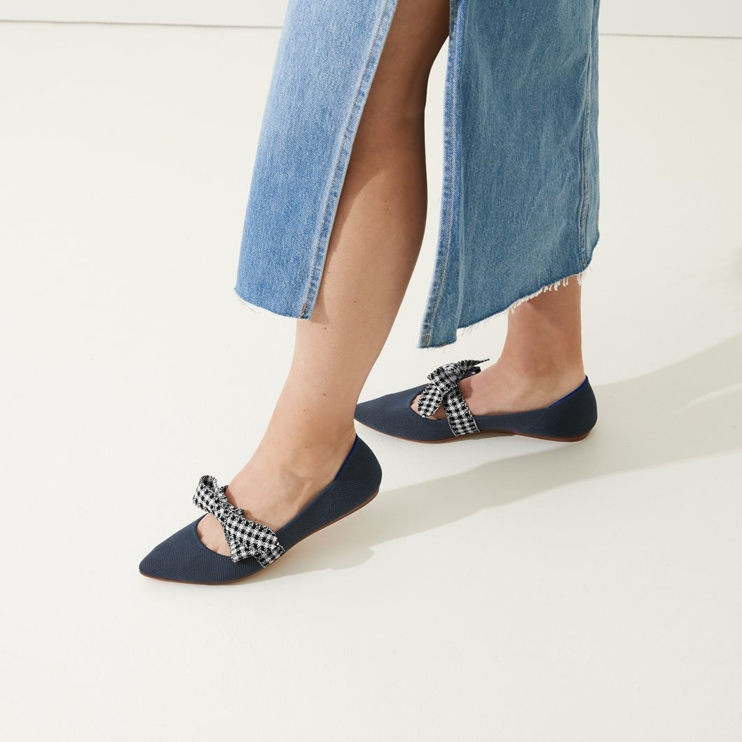 model wearing the pointed flats in navy blue with a blue and white gingham bow across the top