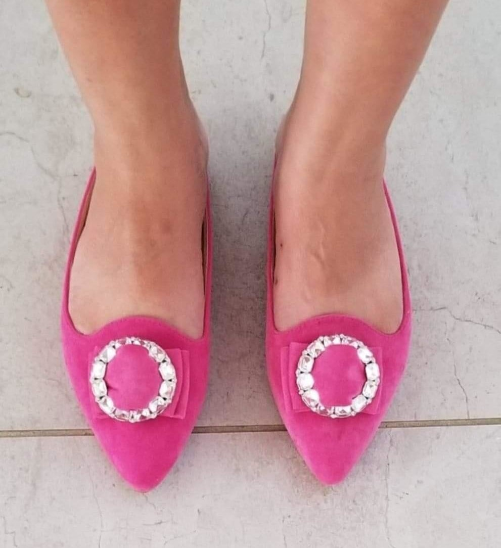 reviewer wearing the pointed-toe slip-on flat with pointed toe in pink suede-like fabric and circular embellishment on top