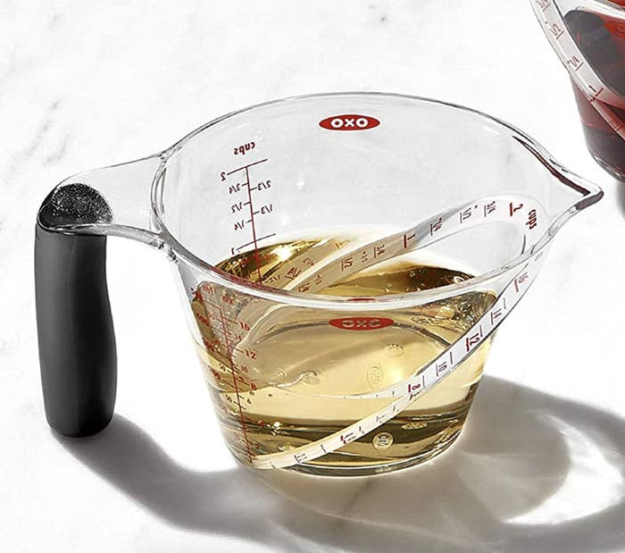 The transparent angled measuring cup with oil inside