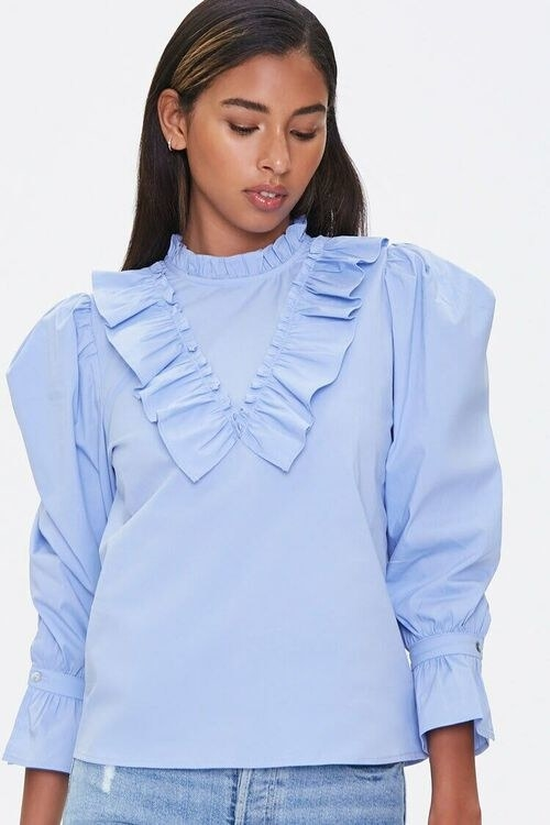 Model wearing the blue three-quarter sleeve top with a mock neck, puff sleeves, and ruffles