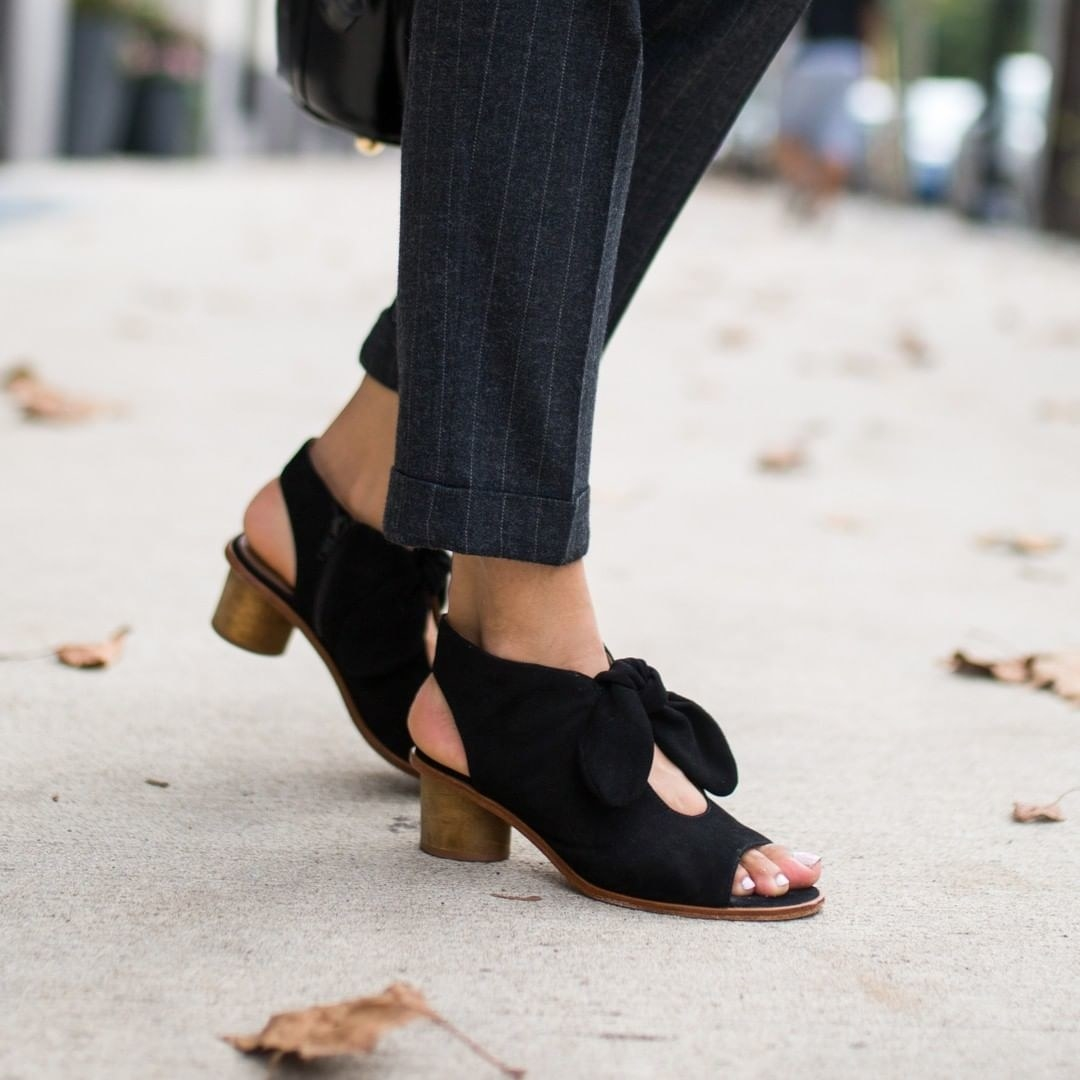 model wearing the open-toe sandal with wooden heel, open in the back and top and a bow on top