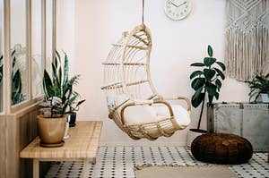 A boho living with with a hanging wicker chair and lots of green plants