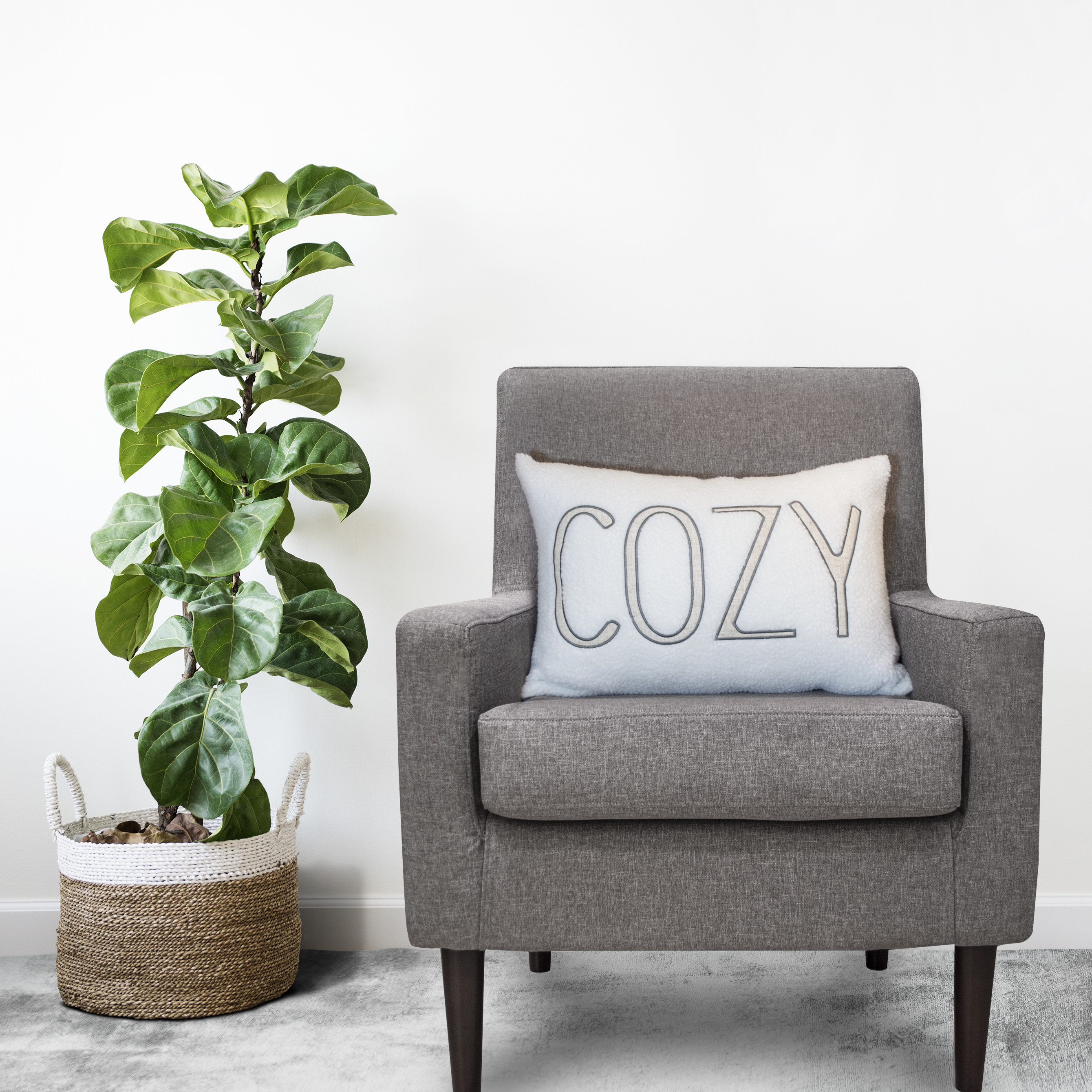 "white pillow with the words ""cozy"" on it and a gray armchair"