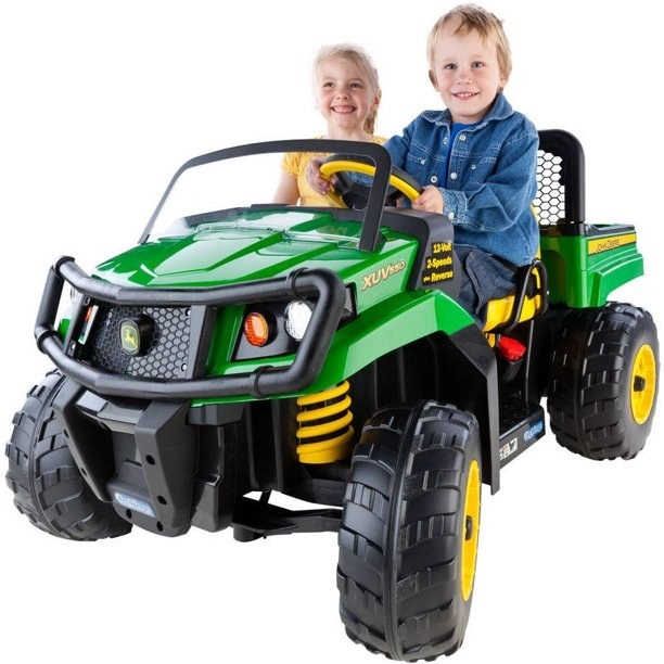 two kids on a green ride-on vehicle