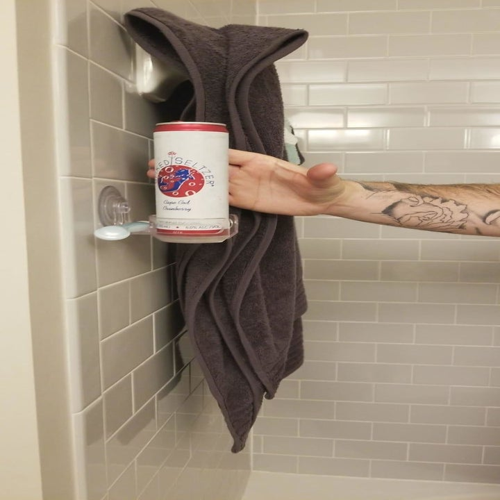 Reviewer reaches for a beer in the drink holder in the shower