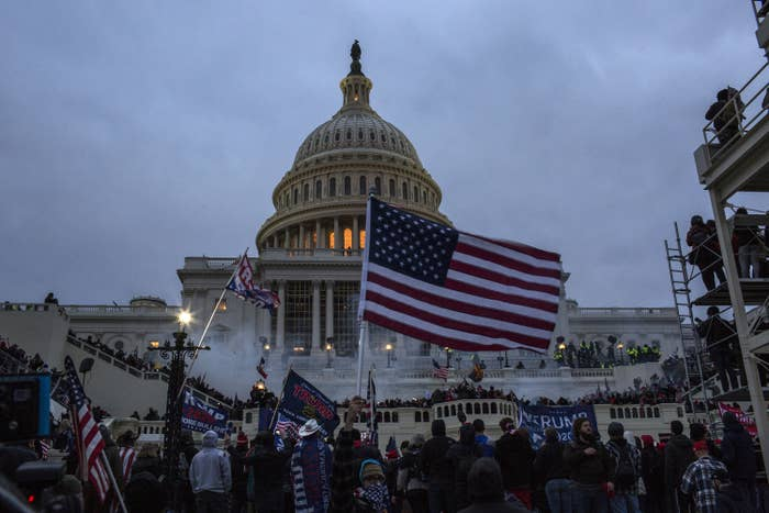 Tear gas surrounds rioters waving American flags in front of the US Capitol at night