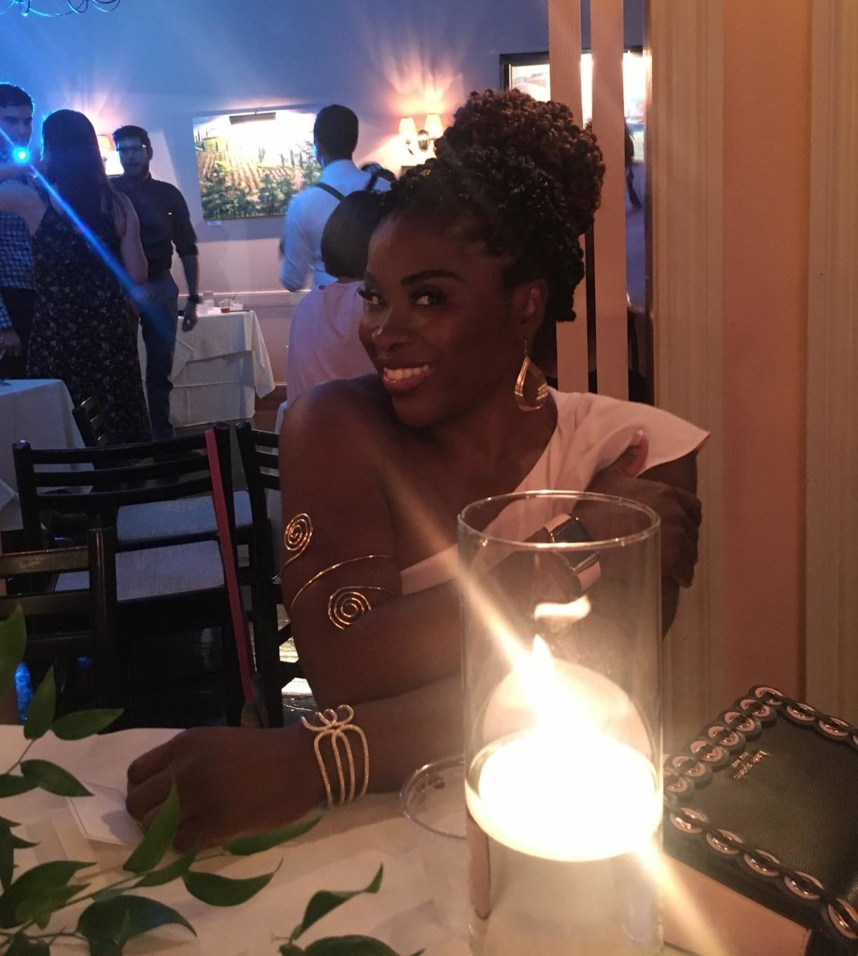reviewer image of a customer wearing the rioso arm cuffs sitting at a candlelit table