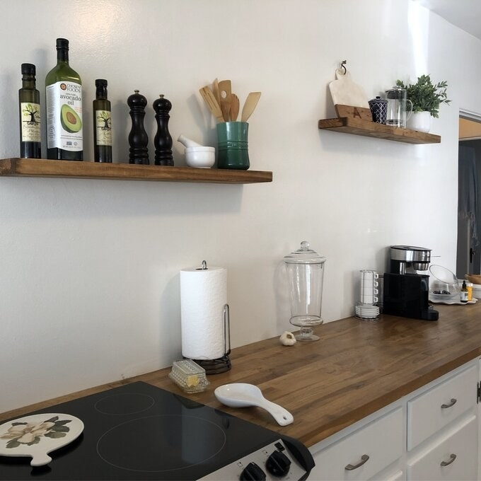 Reviewer's picture of the two wooden shelves in their kitchen