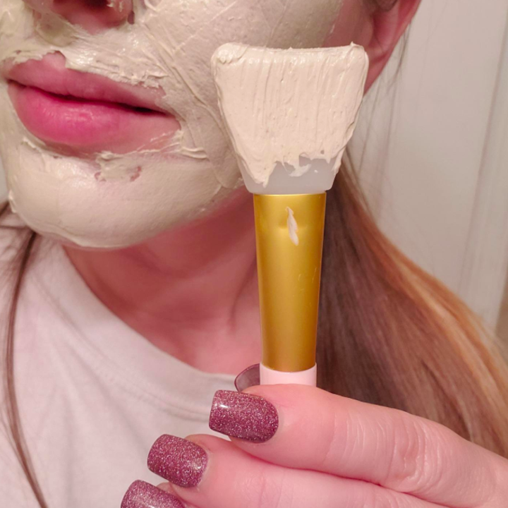 a reviewer holding the brush after using it to apply face mask to their face