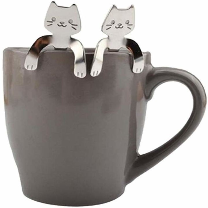 two of the cat spoons in a mug
