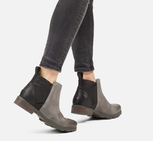 model wearing the boots with a grey front and black heel with brown small heel