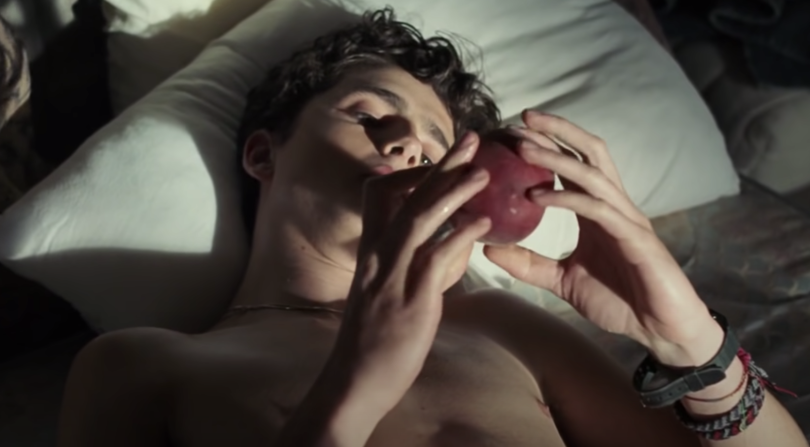 """Timothée Chalamet staring at a peach in bed in """"Call Me by Your Name"""""""